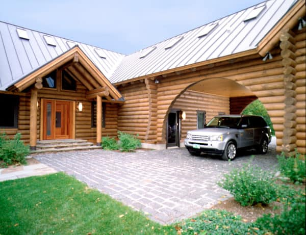 charming wooden log carport with circular silhouette in front of this cabin-style house