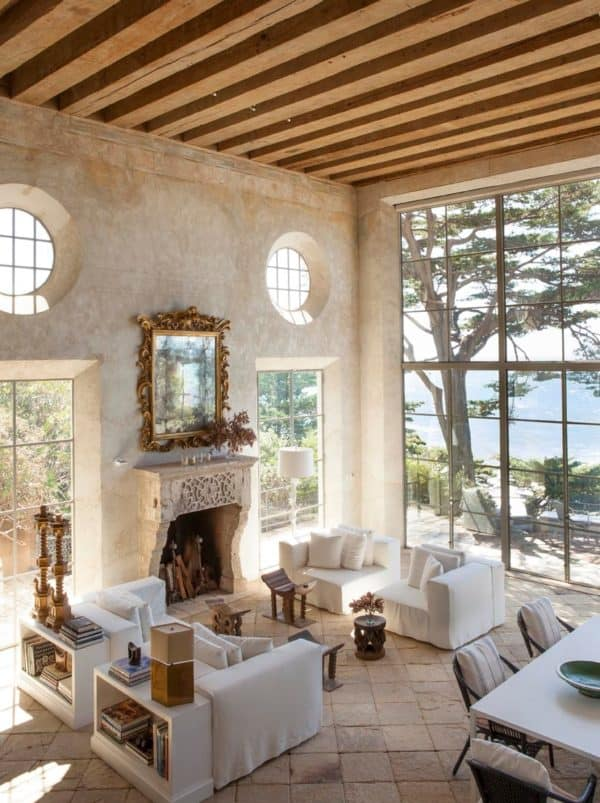 limestone tile floors in front of natural rock fireplace for a breezy, mediterranean-inspired home