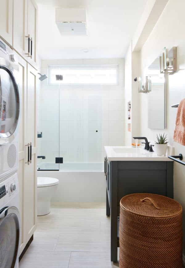 a contemporary bathroom laundry room combo featuring shaker cabinets and black console sink