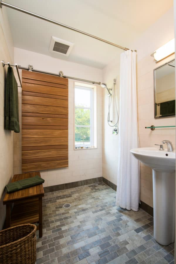 create a unique and cozy bathroom using medium-toned wood window shutters in barn door style