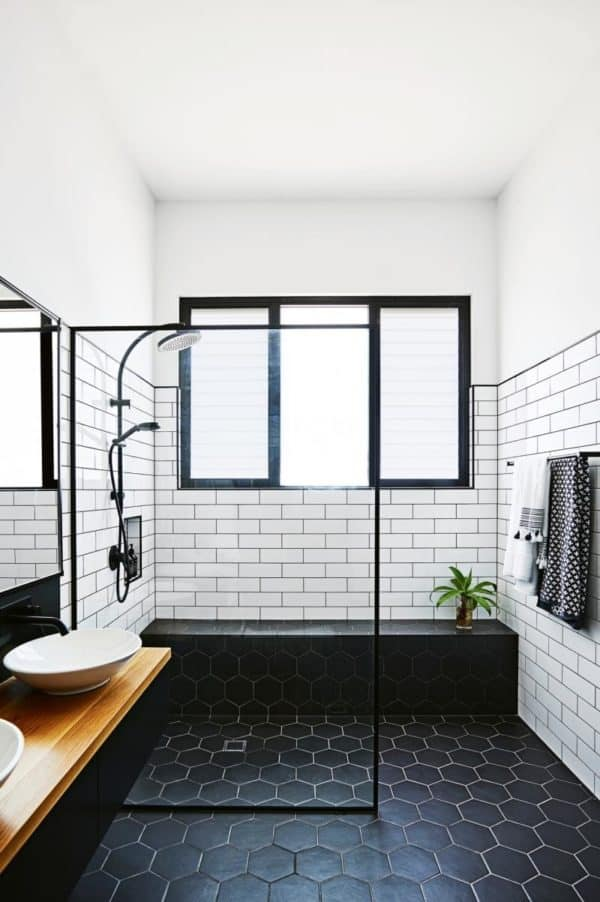 complete a contemporary bathroom with subway tile and black grout for shower walls with a wood floating vanity