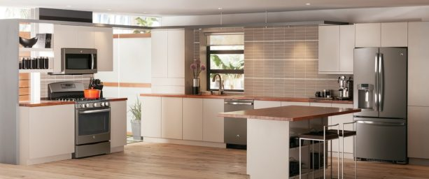 a modern kitchen with slate appliances, white cabinets, and wooden countertops