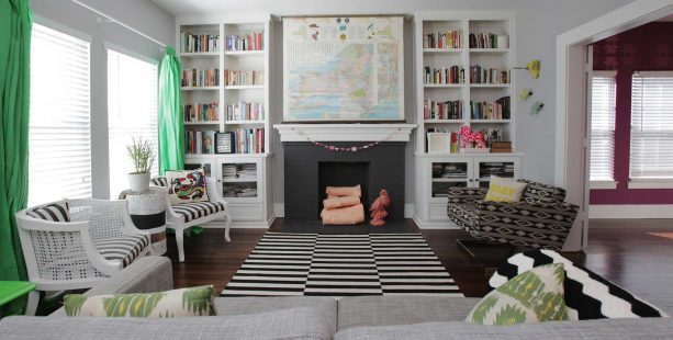 a brick fireplace in black surrounded by two white bookshelves in a classic, eclectic living room