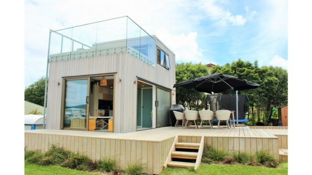a raised-platform tiny house completed with a roof deck with glass railing