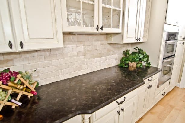 an antique white kitchen cabinets with leathered brown granite countertop