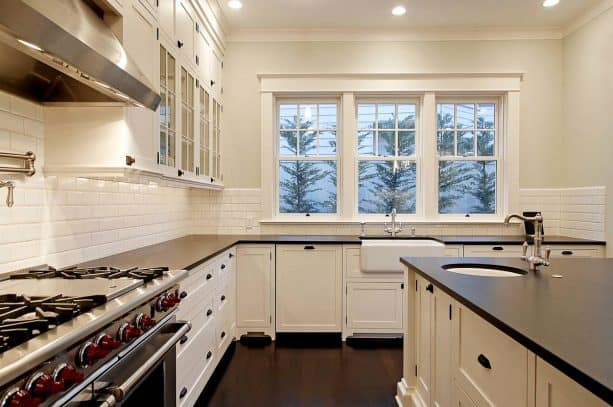 off-white cabinets with black countertops and hardware