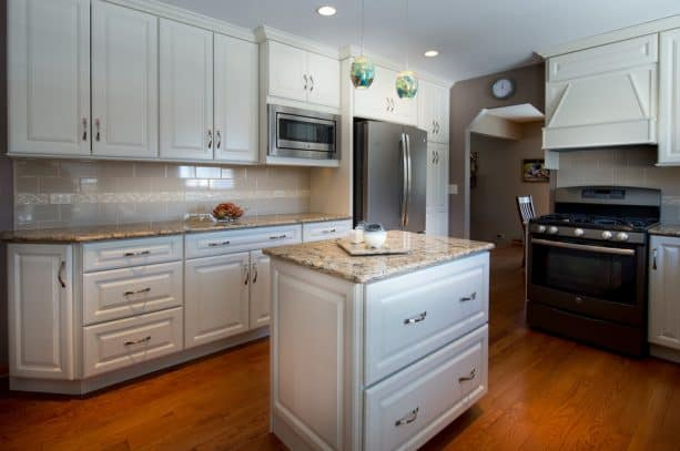 the pairing of slate appliances, white cabinets, and Cambria quartz countertops