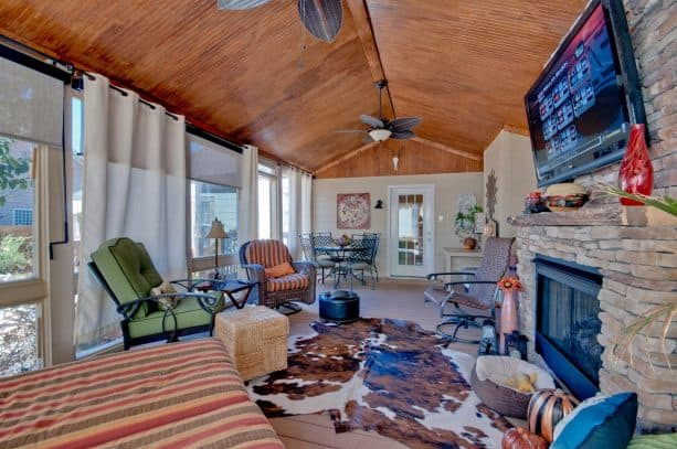 a southwestern screened porch with stone fireplace and white outdoor curtains