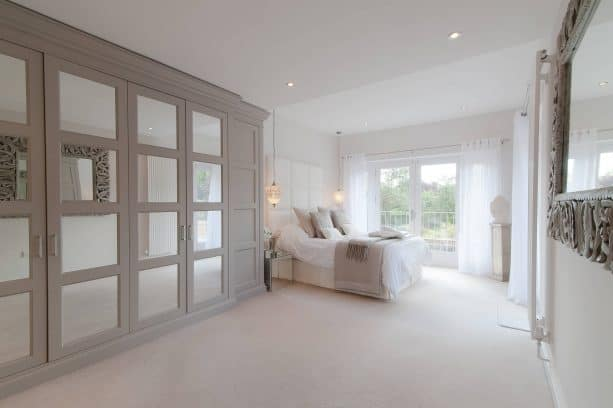 a grey and white bedroom with cream white carpet floor