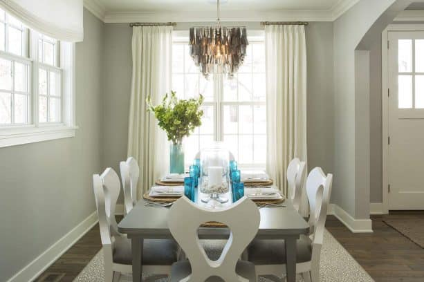beach style dining room with grey wall and reclaimed wood floor