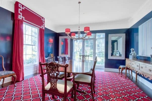 a dining room with rich blue walls and hot pink floor-length curtains