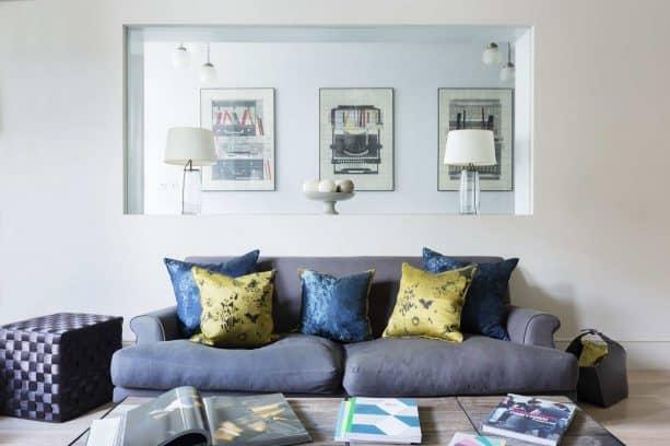 a frameless glass window between living room and hallway