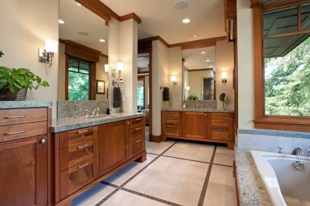 a craftsman bathroom with coordinating vanities and crown molding