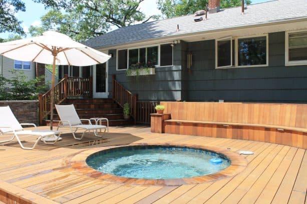 a traditional exterior with dark grey shingle siding and custom cedar deck