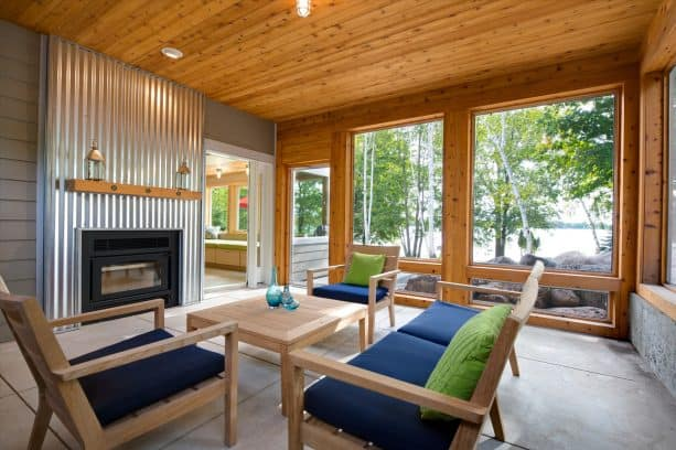 a beach-style screened porch with unique corrugated metal fireplace