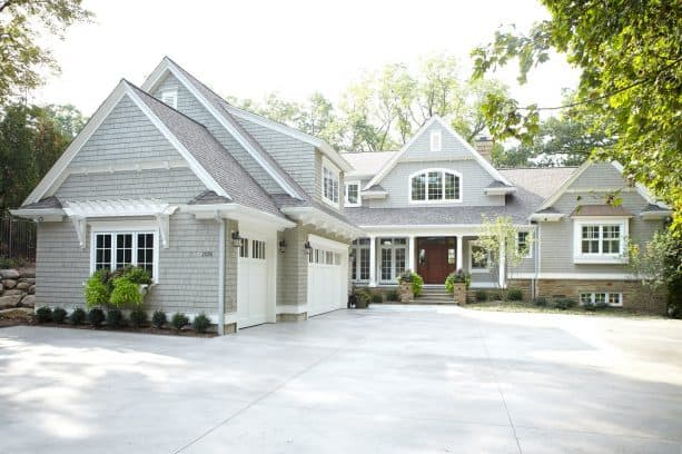 a separated two-story garage in front of a traditional residence