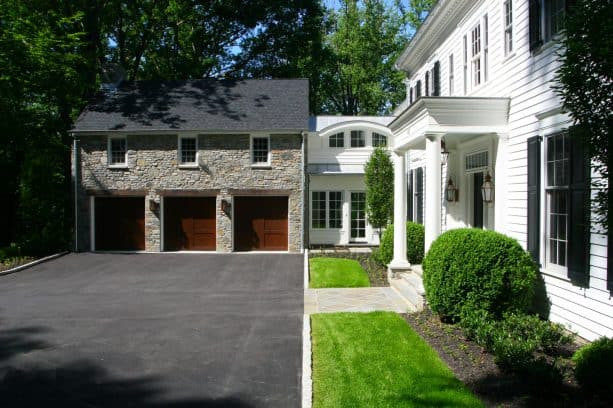 a stone garage located in front of a house with white siding material