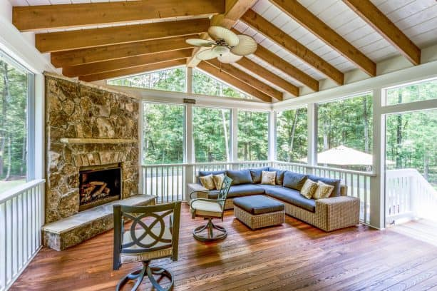 a traditional screened porch with stone fireplace and L-shaped sofa
