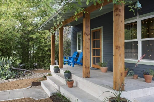 mountain house with dark blue-painted siding and clear-stained douglas fir columns