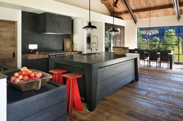 a rustic kitchen with black island, black cabinets, white walls, and red accentuating stools