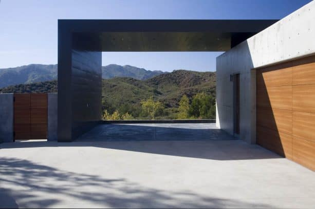 a modern architectural carport with green mountain view at the back
