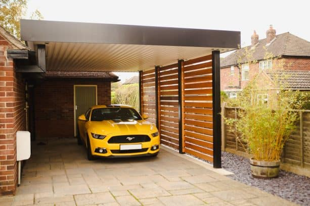 a trendy carport with a wooden privacy screen and a touch of black for boldness