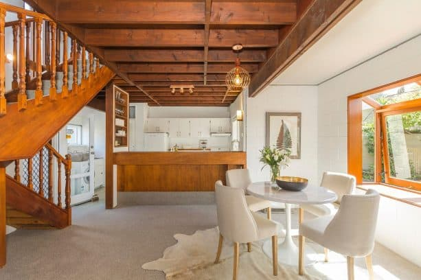 an open kitchen and dining room with white-painted cinder block walls and stained-wood elements