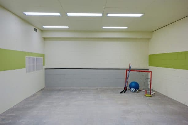fun atmosphere in a indoor kids' sport room with white, grey, and green cinder block walls