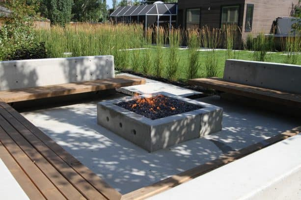 an outdoor living area with fireplace at the end of the concrete walkway