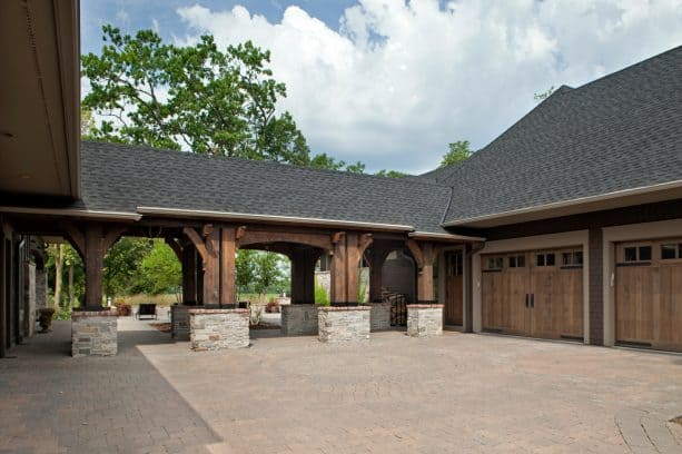 the covered walkway looks gorgeous with the combination of wood and brick as the main materials