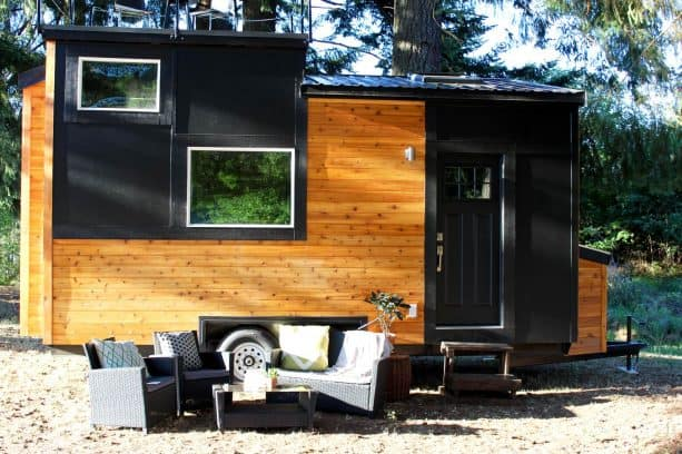 a modern tiny house with small deck on the roof