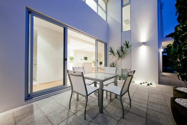 a backyard patio with complete table and chair set for alternative eating place in the modern courtyard house