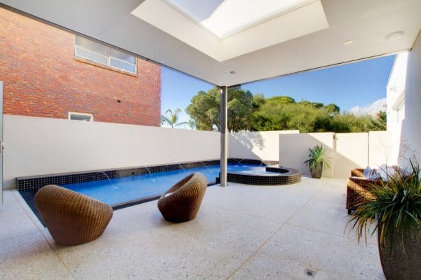 a contemporary pool patio looks trendy with its color theme, frosted-skylight, and light exposed aggregate concrete flooring