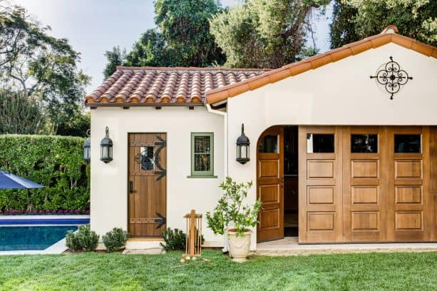 a Mediterranean shed with folding garage door and cozy ivory white exterior