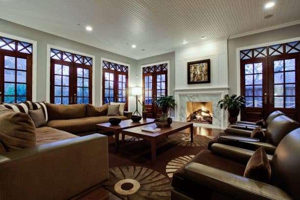 spacious traditional living room with dark wood French style glass doors and windows, white trim and fossil gray wall