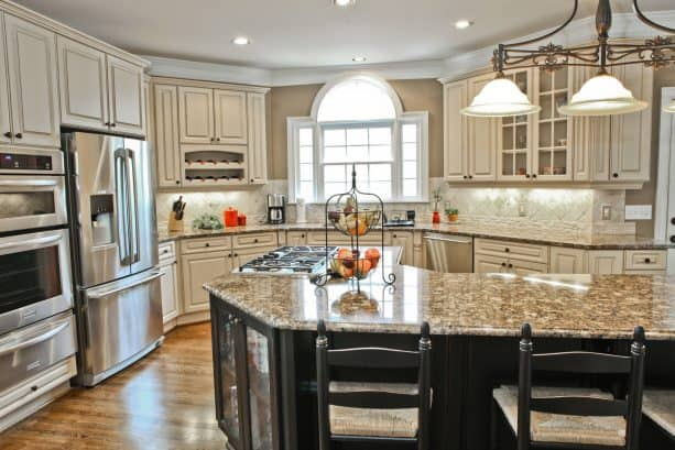 traditional kitchen with antique white cabinets and custom black island