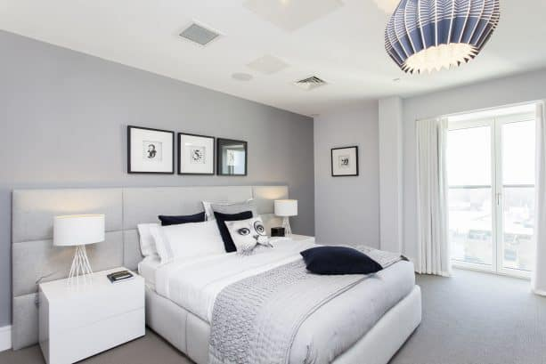 a bedroom with grey wall, white furniture, and grey carpet floor