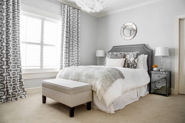 grey and white bedroom with dark mirrored side tables
