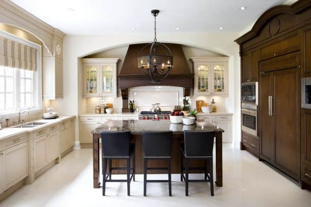 off-white kitchen cabinets paired with dark wood custom cabinets, range hood, and an island
