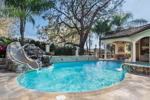 small custom shape inground pool with water slide