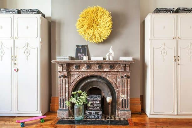 yellow juju hat on grey wall in an eclectic bedroom