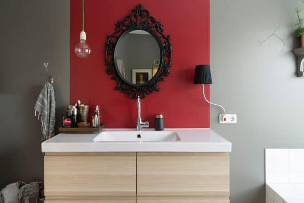a red accent wall with black mirror in an eclectic bathroom