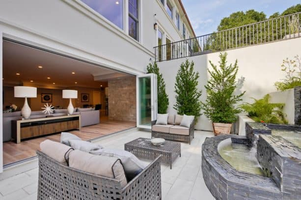 a transitional walkout basement patio with large outdoor living and fountain