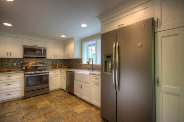 a slate refrigerator placed in a custom white recessed-panel cabinet