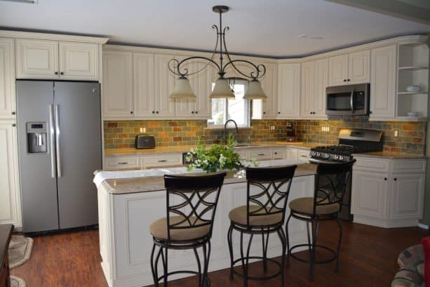 a traditional kitchen with off-white raised panel cabinets and a complete set of slate appliances