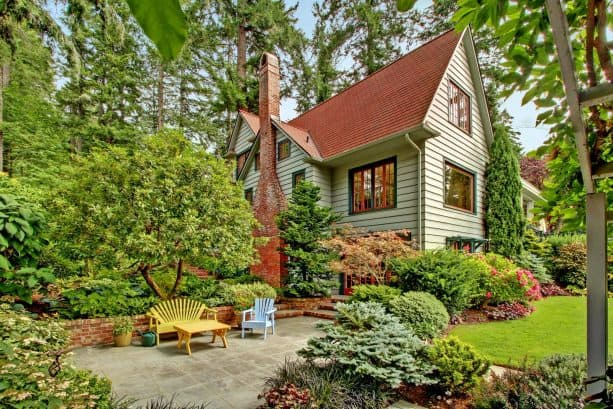 a sage green house with red brick chimney