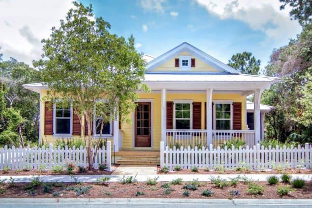 a beach-style exterior with yellow, white, and stained wood tones