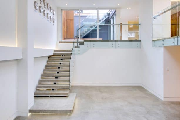 simple yet stunning concrete open staircase directing to the basement area