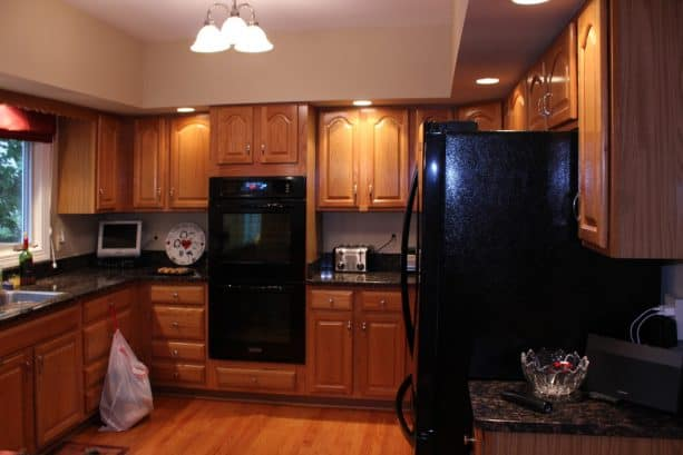 the oak cabinets are paired with black countertops and black appliances