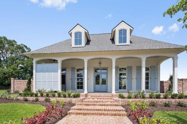 a white brick house with matching grey trim and shutters